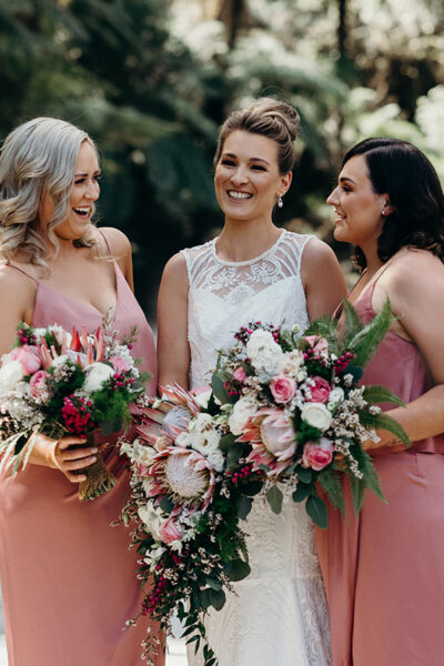 Bride and bridesmaids holding native flowers for wedding